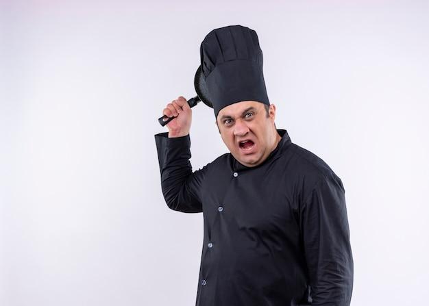 Boze mannelijke chef-kok die zwarte uniform draagt en kookhoed die een pan met agressieve uitdrukking slingert die zich over witte achtergrond bevindt