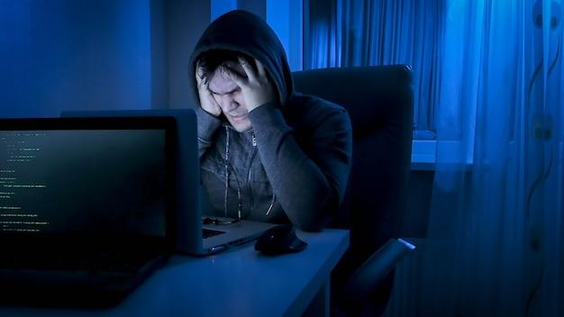 Boze mannelijke hacker in kap hand in hand op zijn voorhoofd terwijl hij 's nachts werkt