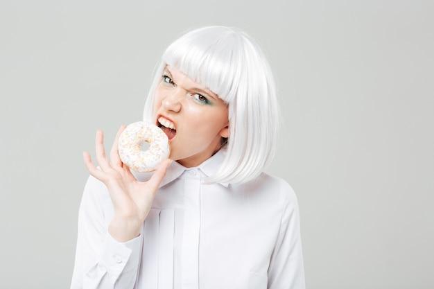Boze mooie jonge vrouw met blond haar die verse donut eet
