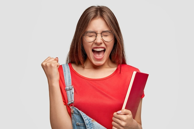 Boze, nerveuze vrouw schreeuwt geïrriteerd, balt vuist, houdt mond wijd open, drukt haar woede uit