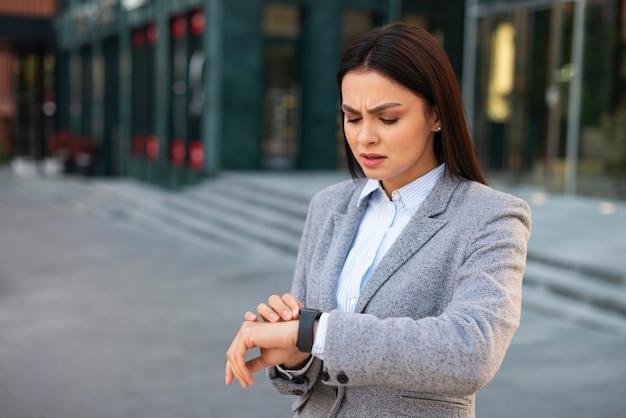 Boze onderneemster die haar horloge met exemplaarruimte bekijkt