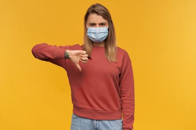 Boze, ongelukkige jonge vrouw in virusbeschermend masker op gezicht tegen coronavirus staan en duimen omlaag geïsoleerd over gele muur tonen