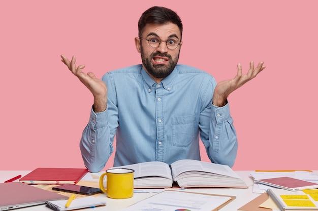 Boze ongeschoren ontevreden man spreidt handen, voelt zich ontevreden en geen idee, leest de encyclopedie, zit op de werkruimte, drinkt thee