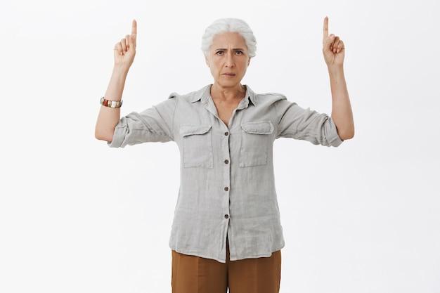 Boze, ontevreden grootmoeder die met de vinger omhoog wijst en er teleurgesteld uitziet