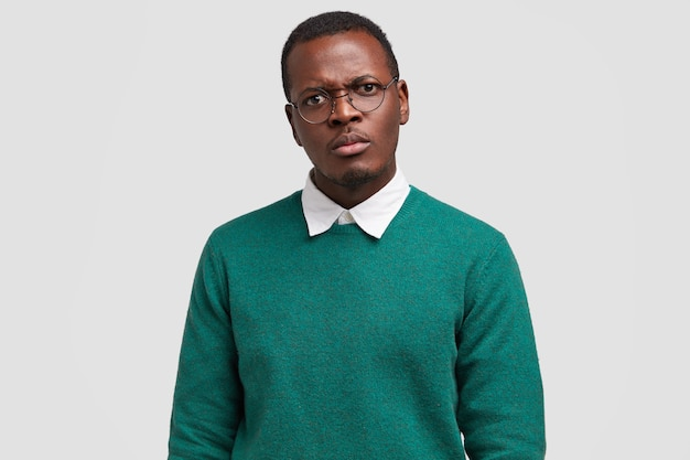 Boze ontevreden zwarte man fronst gezicht heeft gezichtsuitdrukking teleurgesteld, geërgerde blik, gekleed in groene trui