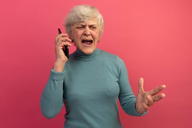 Boze oude vrouw die blauwe coltrui draagt en aan de telefoon praat terwijl ze haar hand in de lucht houdt en naar beneden kijkt