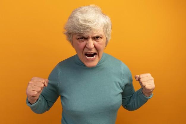 Boze oude vrouw die een blauwe coltrui draagt en vuisten balt en schreeuwt