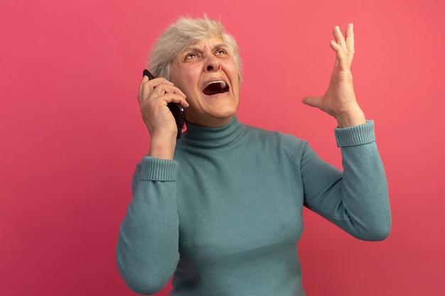 Boze oude vrouw met een blauwe coltrui die aan de telefoon praat en omhoog kijkt terwijl ze de hand opsteekt, geïsoleerd op een roze muur