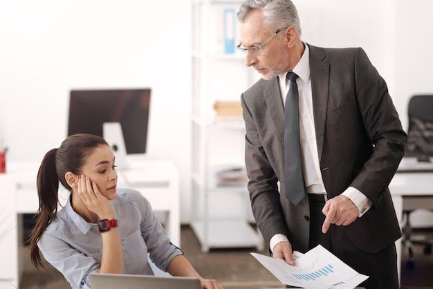 Boze oudere man die documenten in de rechterhand houdt terwijl hij een nieuwe taak geeft, naast zijn werknemer