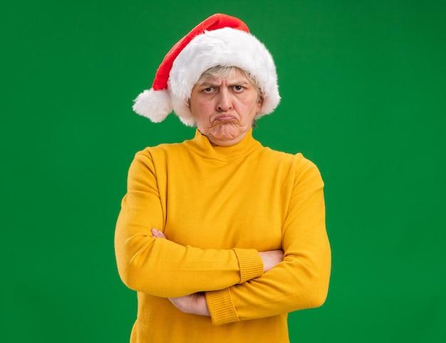 Boze oudere vrouw met kerstmuts staande met gekruiste armen geïsoleerd op paarse achtergrond met kopie ruimte
