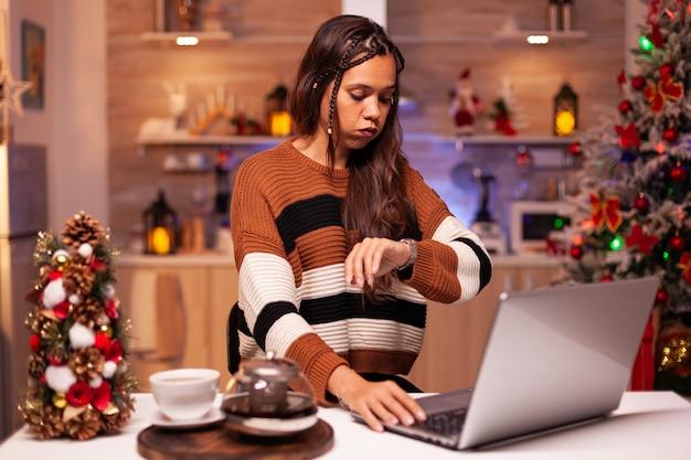 Boze persoon aan het werk op kerstavond met laptop