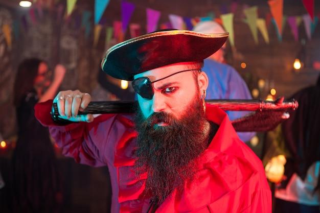 Boze piraat die halloween viert met zijn vrienden. man verkleed als een piraat met een grote hoed.
