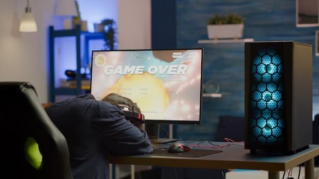 Boze pro-vrouwengamer die space shooter-videogame verliest tijdens online kampioenschap. cyberspeler test virtuele videogames met behulp van krachtige pc in speelkamer tijdens esports-toernooi