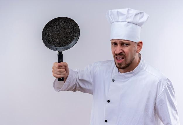 Boze professionele mannelijke chef-kok in wit uniform en kokhoed die een pan houdt die ontevreden status over witte achtergrond kijkt
