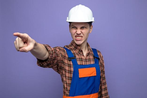 Boze punten naar voren, jonge mannelijke bouwer die uniform draagt