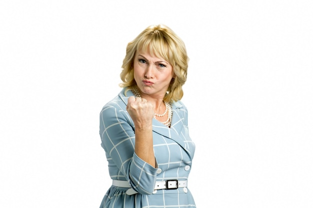 Boze rijpe vrouw die een vuist maakt. fronsende blanke vrouw die vuist over wit ophangen.