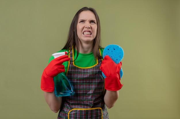 Boze schoonmakende jonge vrouw die eenvormig in rode handschoenen draagt die schoonmakende nevel met spons op geïsoleerde groene muur houden