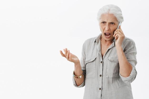 Boze senior vrouw schreeuwen tijdens het gesprek op de mobiele telefoon