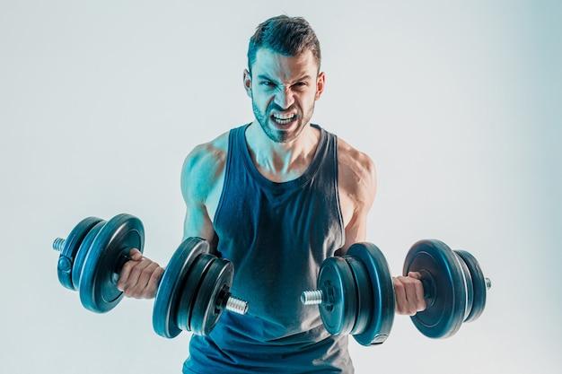 Boze sportman die biceps-spieren traint met halters. jonge, bebaarde europese man draagt sportuniform en kijkt naar de camera. geïsoleerd op turkooizen achtergrond. studio opname. ruimte kopiëren