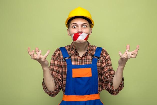 Boze spreidende handen jonge mannelijke bouwer met uniform verzegelde mond met ducttape