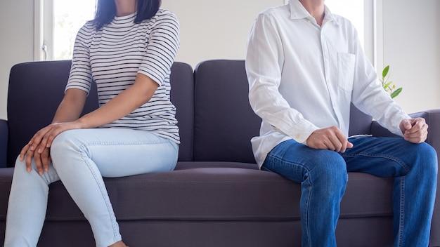 Boze stellen zitten na een ruzie apart op de bank in de woonkamer. het probleem van liefde na het huwelijk dat tot echtscheiding leidt