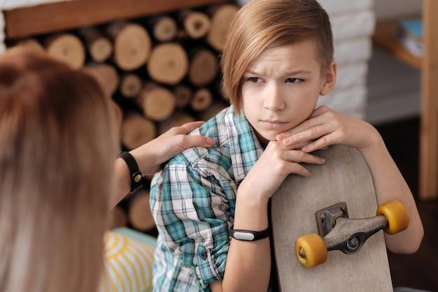 Boze stijlvolle jonge patiënt die handen houdt in de buurt van het gezicht dat fitnessarmband draagt aan de rechterkant die zijn voorhoofd rimpelt