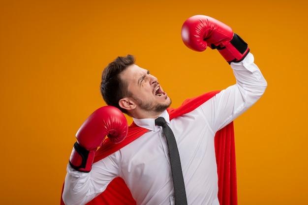 Boze super heldzakenman in rode cape en in bokshandschoenen die handen opheffen die kracht en moed tonen die zich over oranje achtergrond bevinden
