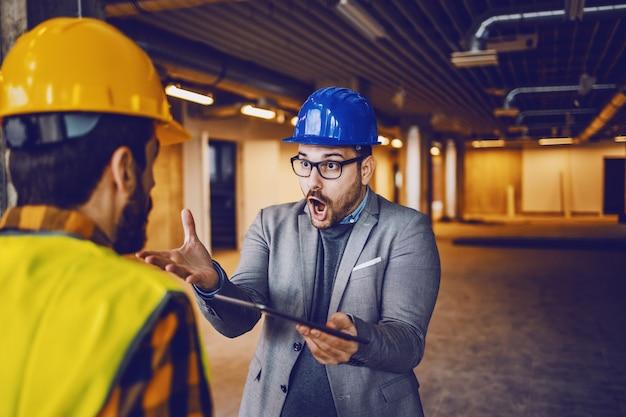 Boze supervisor die tegen zijn arbeider schreeuwt omdat hij een fout heeft gemaakt bij de bouw. bouwen in bouwproces interieur.