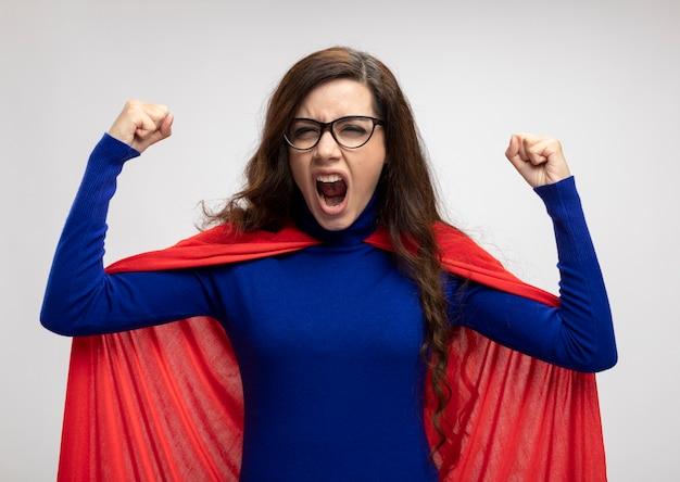 Boze supervrouw met rode cape in optische glazen houdt vuisten omhoog geïsoleerd op witte muur