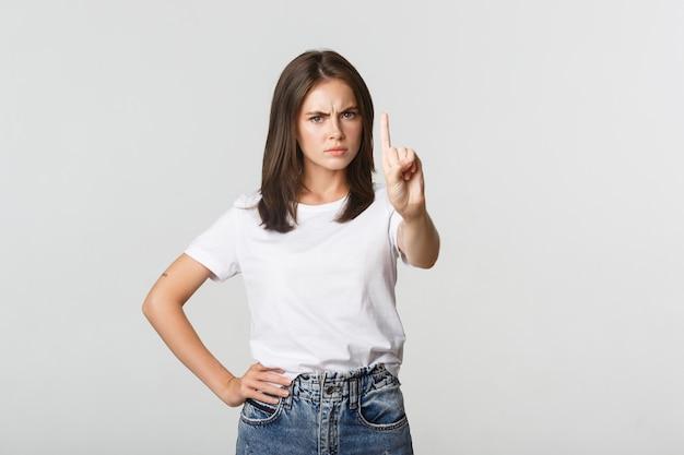 Boze teleurgestelde vrouw die vinger in afkeuring schudt, persoon die verkeerde beslissing uitscheldt.