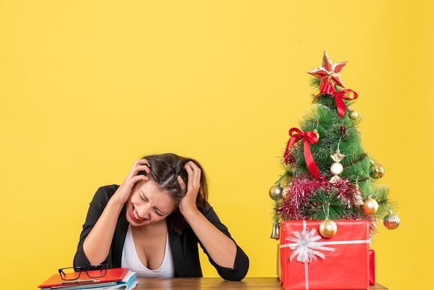 Boze, uitgeputte en nerveuze jonge vrouw zittend aan een tafel in de buurt van versierde kerstboom op kantoor op geel