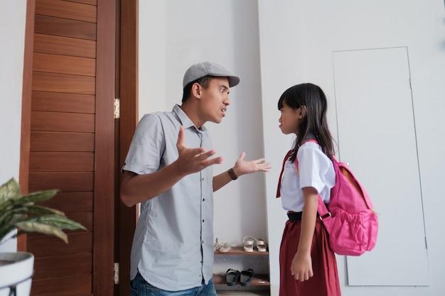 Boze vader confronteert zijn kind na school. aziatische primaire student probleem. gewelddadige ouder met dochter