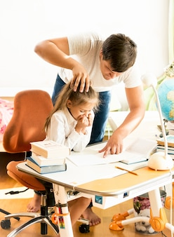 Boze vader wijzend op fout op dochters notitieboekje