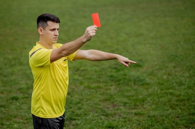 Boze voetbalscheidsrechter die een rode kaart toont en met zijn hand op penalty wijst.