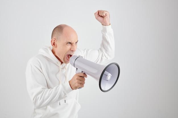 Boze volwassen man in witte hoodie schreeuwt in megafoon en eist gerechtigheid
