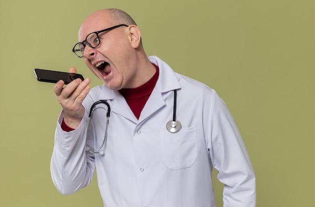 Boze volwassen man met bril in doktersuniform met stethoscoop die tegen iemand aan de telefoon schreeuwt