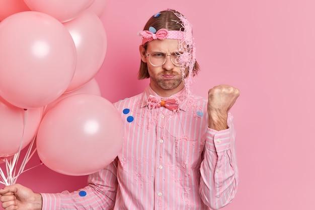 Boze volwassen man toont gebalde vuist belooft je te straffen besmeurd met crème heeft sombere uitdrukking gekleed in elegant overhemd vlinderdas komt op verjaardagsfeestje houdt ballonnen vast