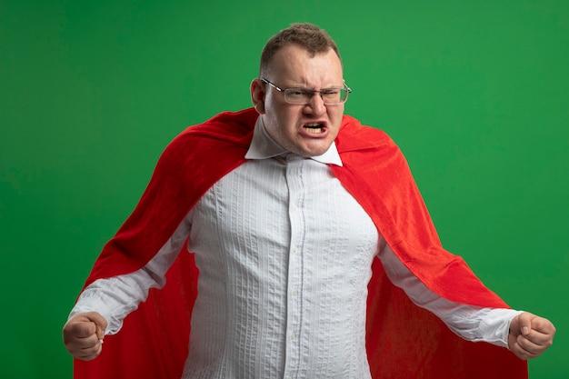 Boze volwassen superheld man in rode cape bril gebalde vuisten kijken kant geïsoleerd op groene muur