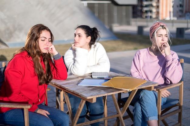 Boze vrienden of kamergenoten die buiten in een café zitten