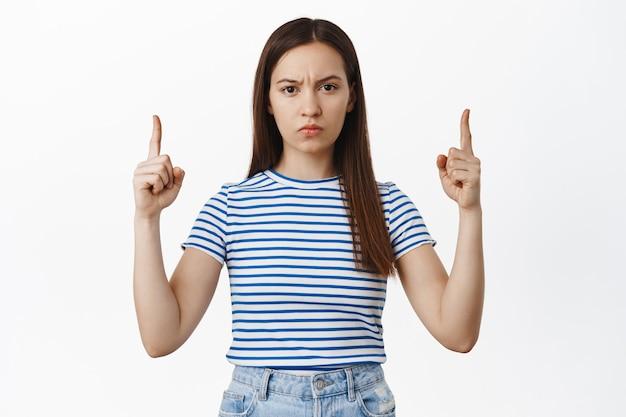 Boze vriendin fronst, wijst met de vingers omhoog met een boos gezicht, houdt niet van, klaagt over iets slecht, vreselijke banner, staat gefrustreerd tegen een witte muur