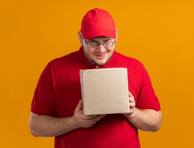Boze vrolijke overgewicht jonge bezorger in optische bril steekt tong uit met kartonnen doos geïsoleerd op oranje muur met kopieerruimte