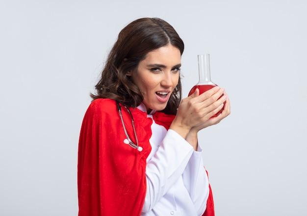 Boze vrolijke supervrouw in doktersuniform met rode cape en stethoscoop houdt rode chemische vloeistof in glazen kolf geïsoleerd op witte muur