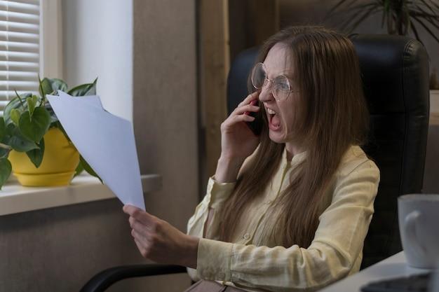Boze vrouw baas praten over de telefoon en schreeuwen, documenten vasthouden. directeur scheldt ondergeschikten op smartphone.