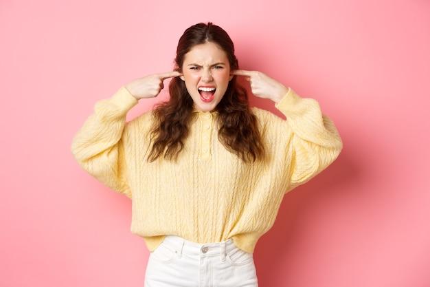 Boze vrouw blokkeert haar oren met vingers en schreeuwt om muziek uit te schakelen geïrriteerd door hard geluid of storend geluid dat tegen de roze muur staat