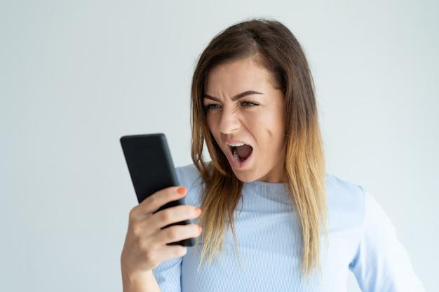 Boze vrouw die bij smartphone schreeuwt. verontwaardigd dame met apparaat.
