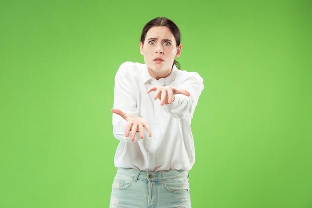 Boze vrouw die camera bekijkt. agressieve zakenvrouw staande geïsoleerd op trendy groene ruimte