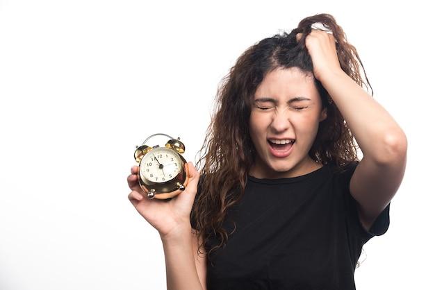 Boze vrouw die haar haar en klok op witte achtergrond houdt. hoge kwaliteit foto