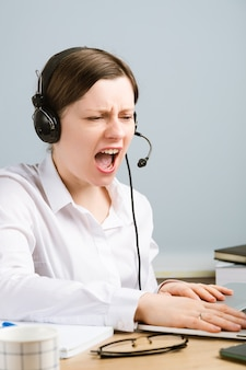 Boze vrouw die tegen tegenstander door hoofdtelefoon schreeuwt. crisistijd op economisch gebied. geërgerde uitdrukking.