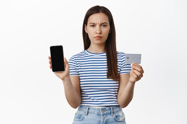 Boze vrouw fronst, toont creditcard en mobiele telefoon leeg scherm, bankrekening of smartphone app-interface, frons wenkbrauwen ontevreden, witte muur.