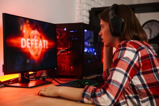 Boze vrouw gamer zittend aan tafel, online spelen op een computer binnenshuis